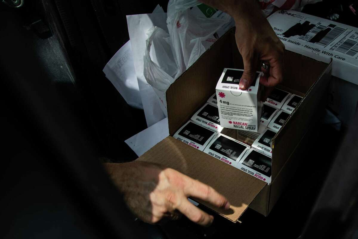 Houston Harm Reduction Alliance vice president Casey Malish picks up a box of Narcan nasal spray to deliver along with unused syringes.