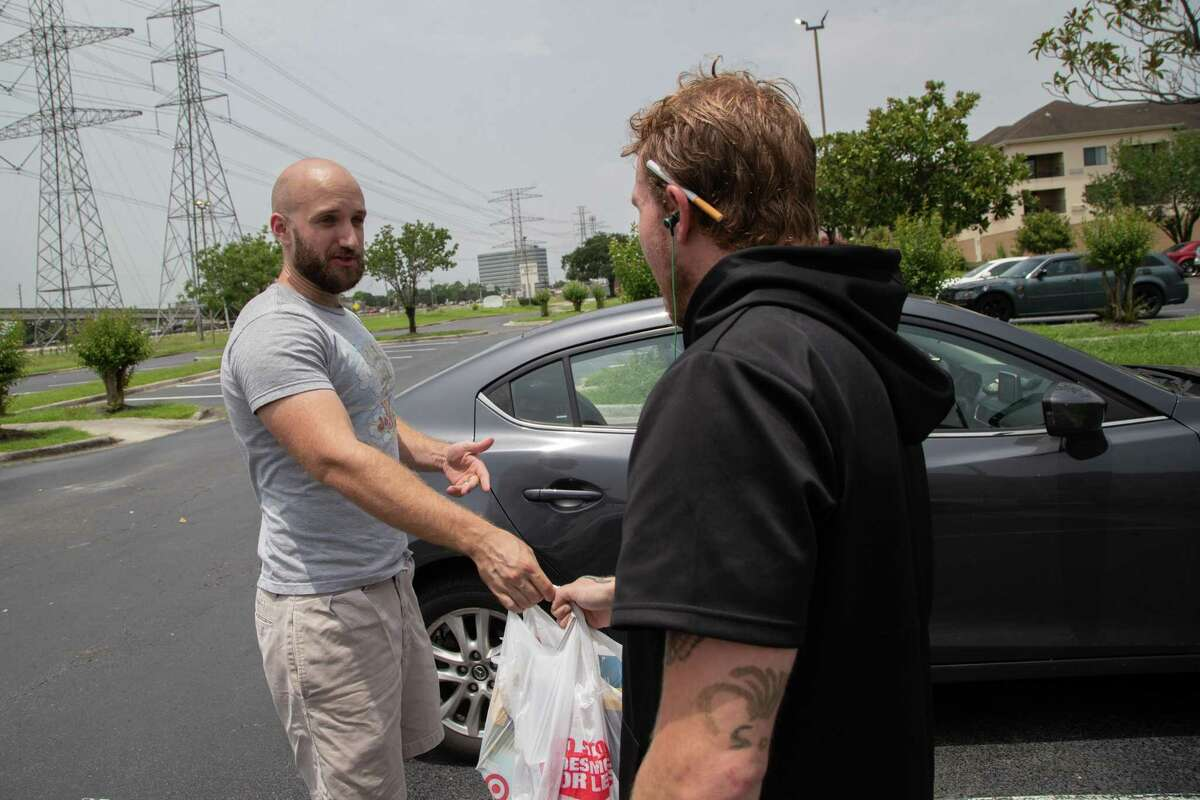 Houston Harm Reduction Alliance vice president Casey Malish delivers a bag that contains a box of Narcan nasal spray and unused syringes to a man in Houston.