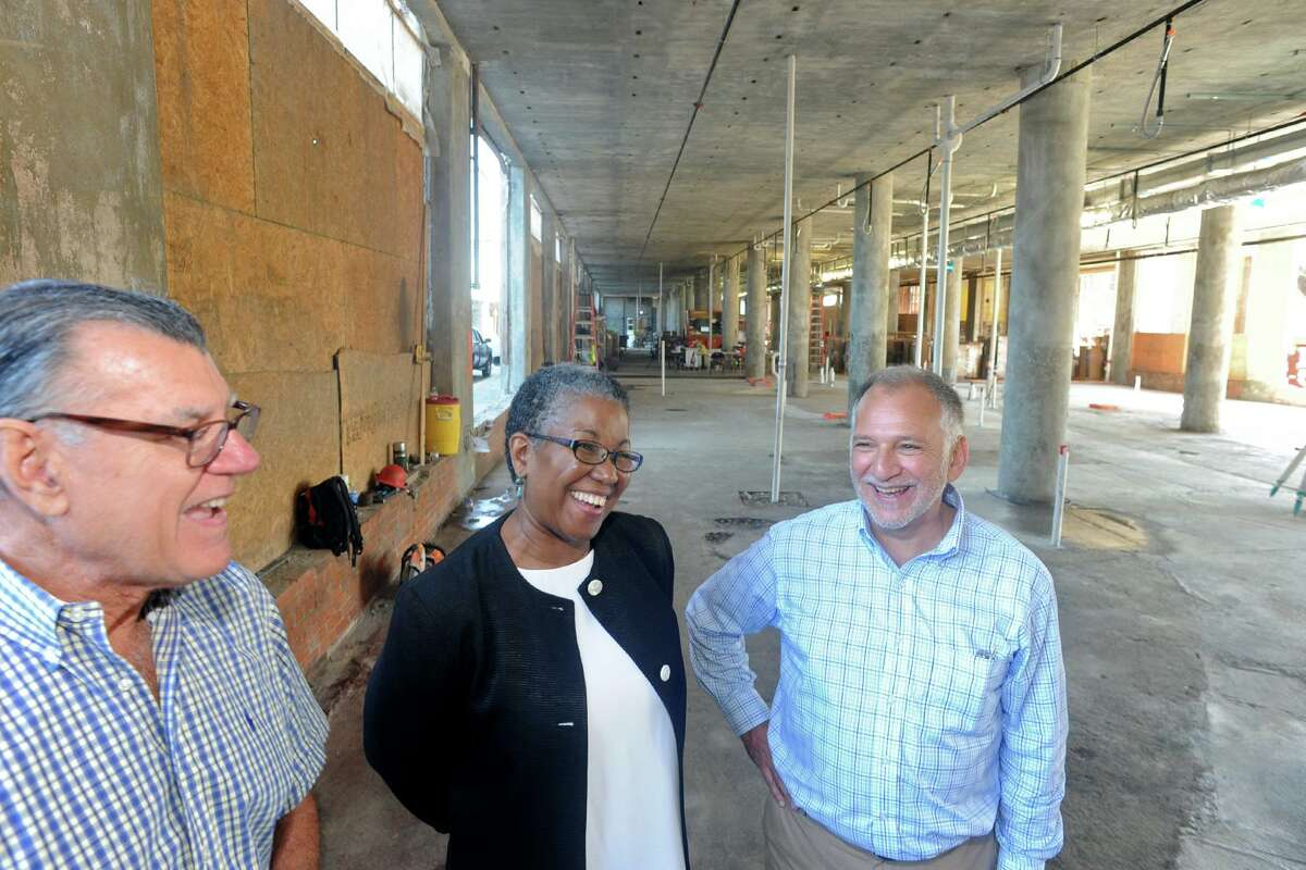 Carol Nixon, center, head of the AFL-CIO's Housing Investments Trust, stands with developers Geof Ravenstine, left, a Gary Flocco, right, at the Cherry Street Lofts project in Bridgeport in 2017.