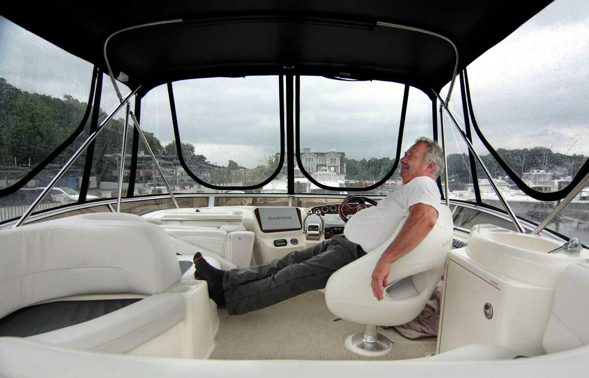 """A storm passes through as avid boater Chris Trentini exclaims, """"The life of a boater when you have nothing to do"""" as he hangs out on his boat with his family at Beacon Point Marina in Greenwich on Thursday."""