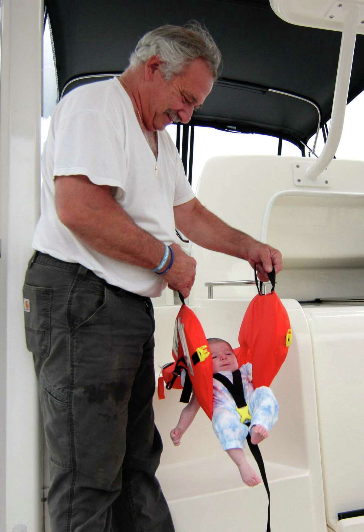 Avid boater Chris Trentini hold his five-week-old granddaughter Charlotte Murray wrapped in a lifevest on his boat Donna Marie at Beacon Point Marina. Because of storms that passed through the region, the family decided to just hang out on the boat in port.