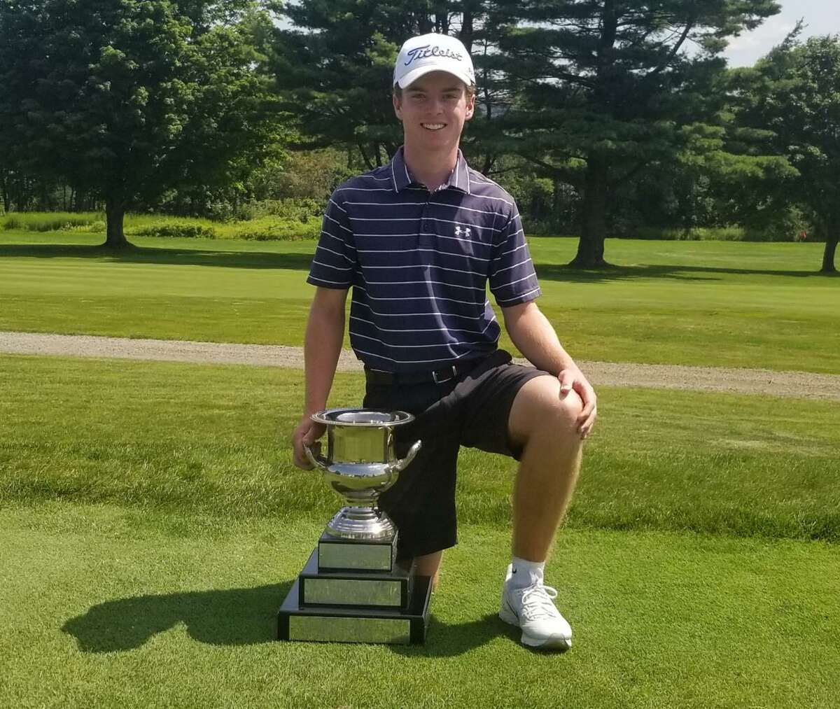 Connor Goode kneels next to the trophy after winning the 80th Connecticut Junior Amateur championship at Watertown Golf Club on Friday.