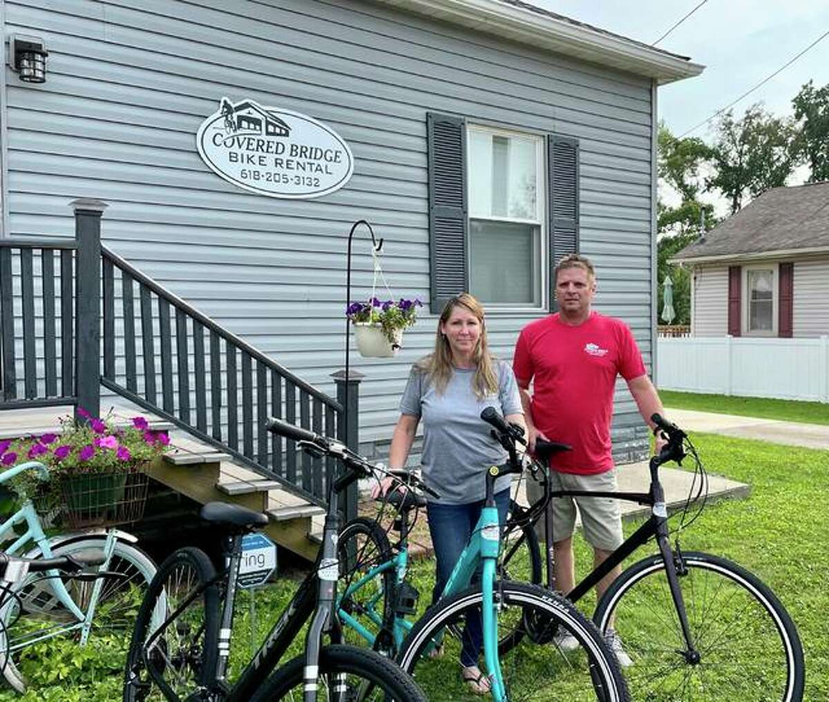 Owners of Covered Bridge Bike Rental Teri and Chris Moore stand in front of their store front with a couple of their rental bikes. Covered Bridge Bike Rental is located in downtown Glen Carbon across the street from the library.