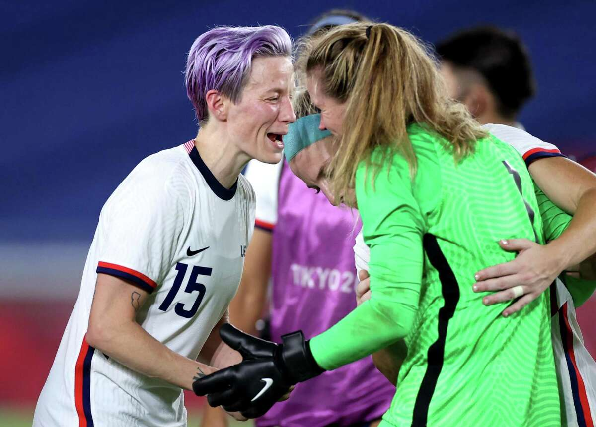 YOKOHAMA, JAPAN - JULY 30: Megan Rapinoe #15 and Alyssa Naeher #1 of Team United States celebrate following their team's victory in the penalty shoot out after the Women's Quarter Final match between Netherlands and United States on day seven of the Tokyo 2020 Olympic Games at International Stadium Yokohama on July 30, 2021 in Yokohama, Kanagawa, Japan. (Photo by Laurence Griffiths/Getty Images)