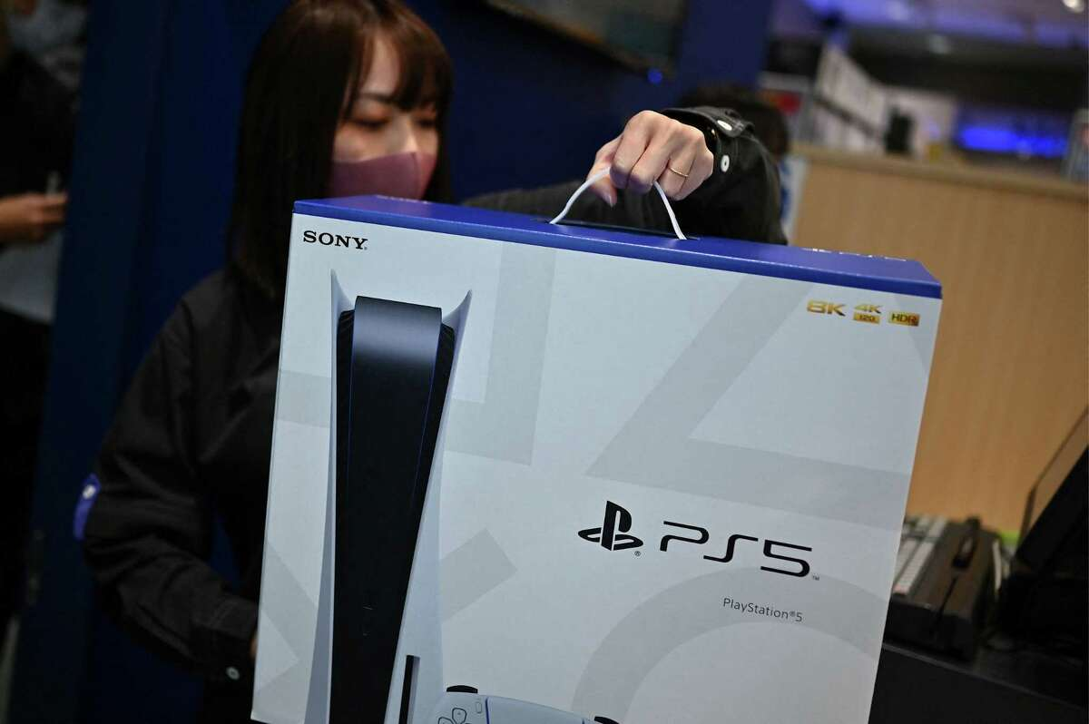 An employee prepares the new Sony PlayStation 5 gaming console for a customer on the first day of its launch last year.