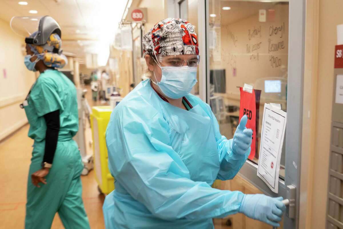 Memorial Hermann Hospital respiratory therapist Angela Detert prepares to enter a patient's room inside a 38-bed ICU treating mostly COVID patients, Tuesday, Jan. 5, 2021, in Houston's Texas Medical Center.