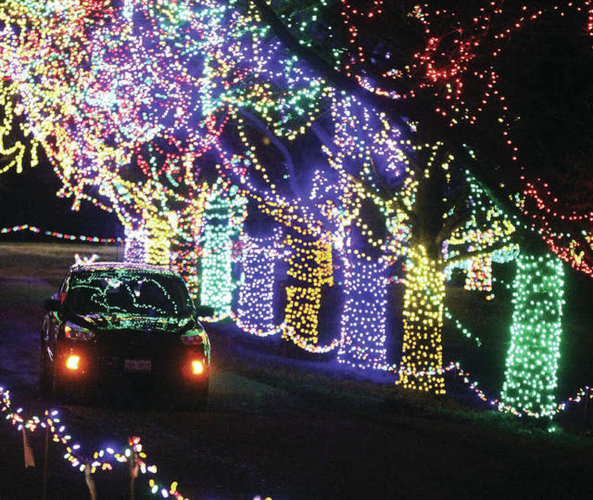 Christmas lights are reflected by a passing car in the upper portion of Christmas Wonderland, the annual holiday light display put on by The Grandpa Gang in Alton's Rock Spring Park during the 2020 opening night in November. An informational meeting for Christmas Wonderland volunteers is set for 11 a.m., Tuesday, Aug. 10 at Meunstermann Pavilion in Gordon Moore Park.