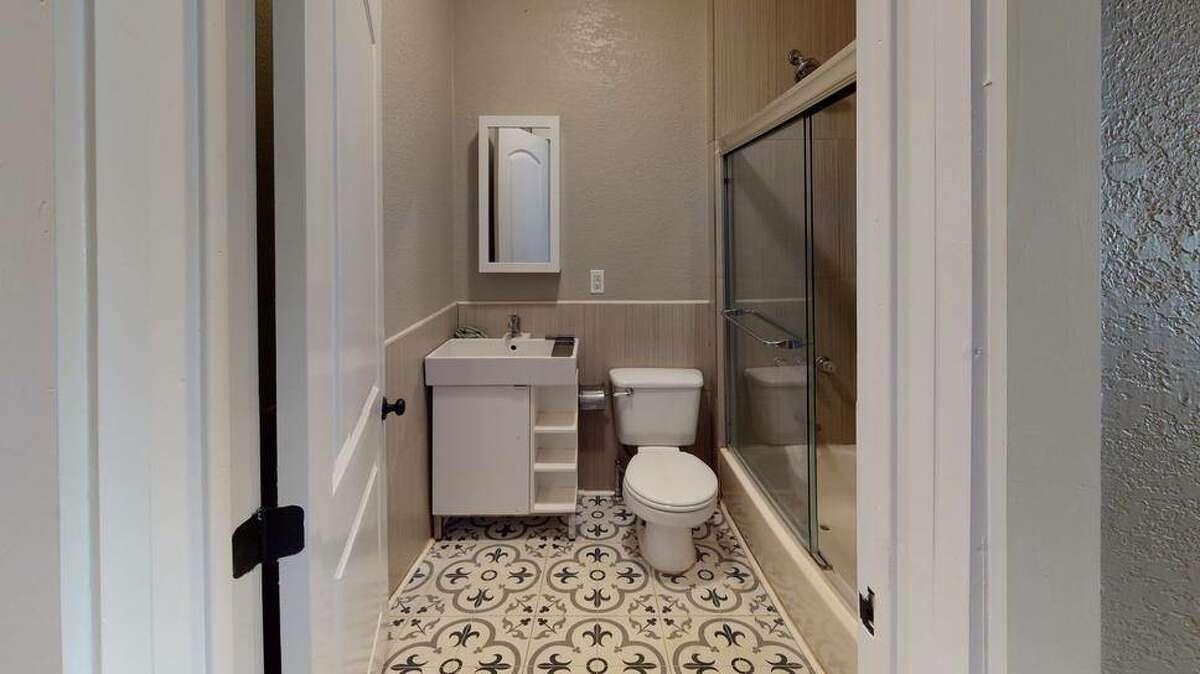 The bathroom is space is a little cozy, but it has unique tile work.