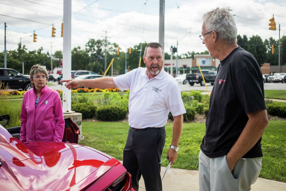 Jeff Pacholka, a sales and leasing consultant at Garber Chevrolet in Midland, center, explains how to activate OnStar as Tom Clark of Sanford, right, and his wife, Cheryl Clark, left, pick up his 38th Corvette, a new red convertible, from the dealership Friday, July 30, 2021. (Katy Kildee/kkildee@mdn.net)