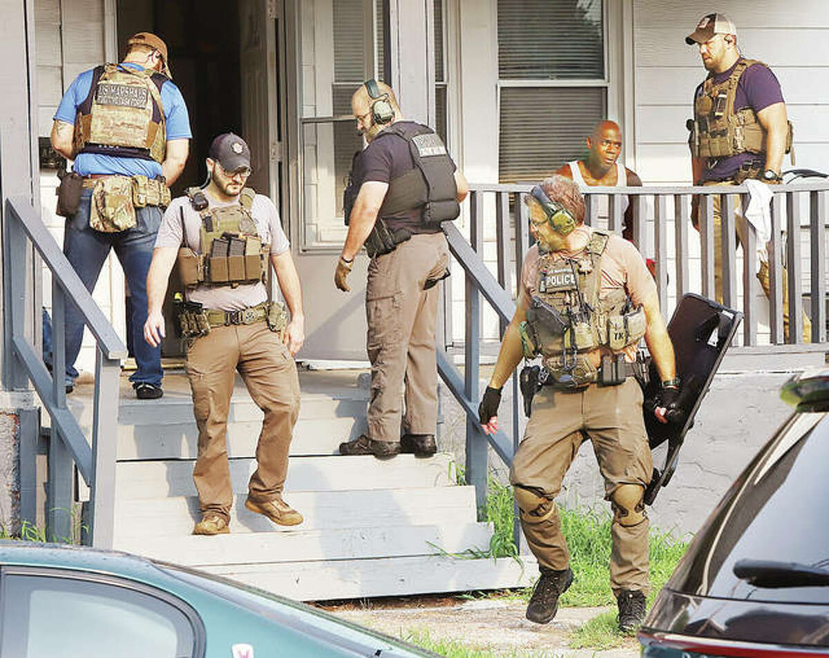 """U.S. Marshals swarmed a house in the 800 block of Haller Street in Wood River Friday morning before 8 a.m. Several people were in the house; one man was taken into custody. Several of the marshals wore vests which indicated they were with the """"Fugitive Task Force."""" Earlier this week marshals assisted Alton Police in arresting 13 people on various charges."""