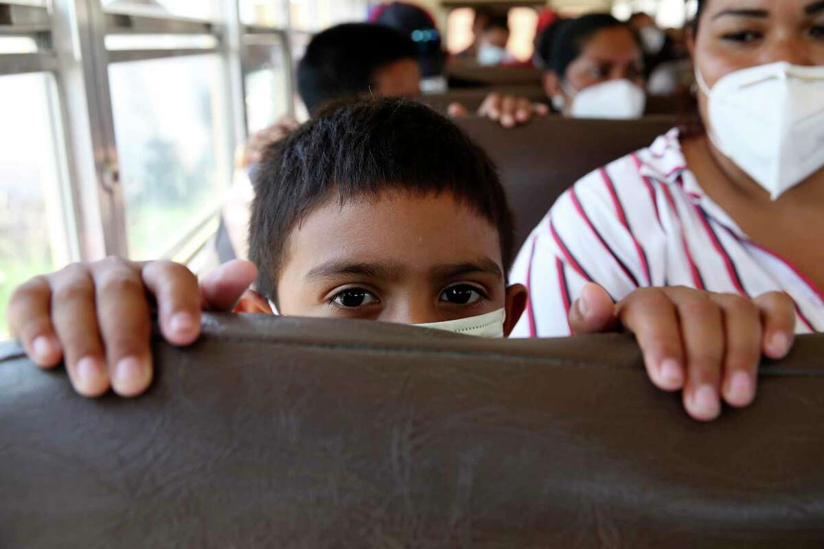 Eight-year-old Austin Brizuela waits on a bus with his mother at Senda de Vida migrant shelter in Reynosa. The migrants were allowed to cross into the U.S. and have their asylum case adjudicated in the U.S.
