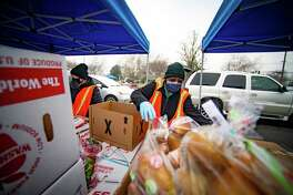 """Volunteers ready boxes of food to load into cars that are waiting at Hiram Johnson High School on Friday, Jan. 8, 2021, at one of the """"touchless"""" food distribution sites run by the Sacramento Food Bank. (Jason Pierce/The Sacramento Bee/TNS)"""