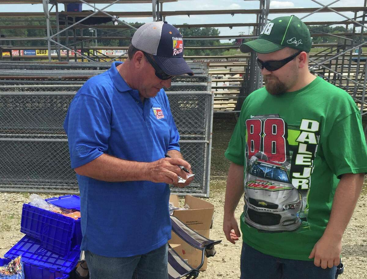 Former NASCAR driver Ken Schrader signs an autograph for a fan at Eldora Speedway in 2015 before the NASCAR Camping World Truck Series MudSummer Classic. Schrader will be racing at Silver Bullet Speedway Aug. 15. (Eric Young/Huron Daily Tribune)