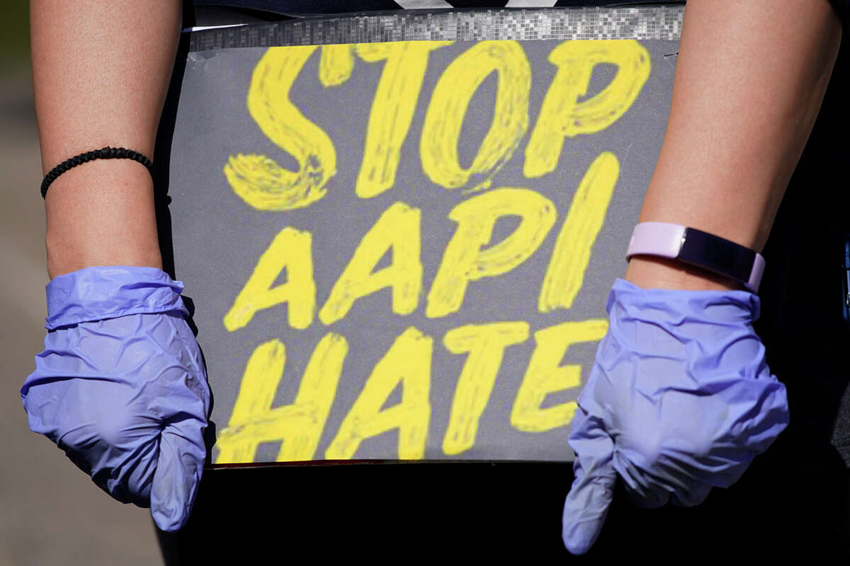 FILE - In this March 20, 2021 photo, a woman holds a sign and attends a rally to support stopping AAPI hate.