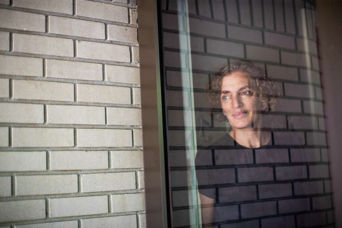 Karen Bernstein, behind her window at home, Thursday, July 29, 2021, in Houston. Bernstein, a retired NASA engineer, was fully vaccinated in February, but about a week ago she got started feeling awfully sick and she tested positive for COVID.