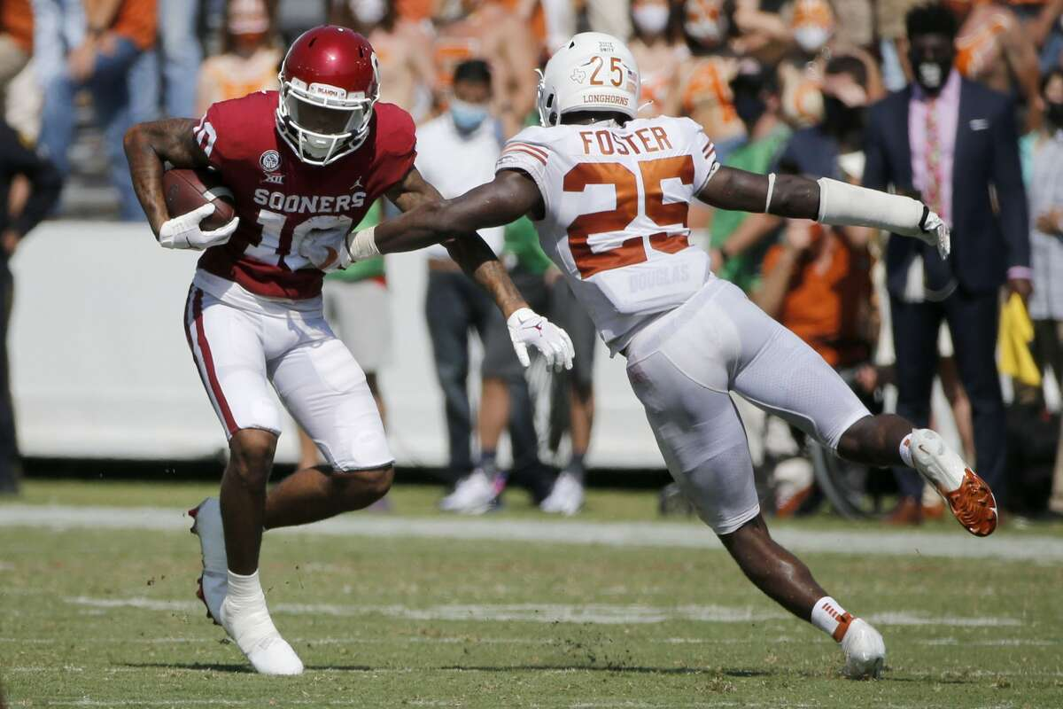 Oklahoma wide receiver Theo Wease (10) evades a tackle by Texas defensive back B.J. Foster (25) during an college football game in Dallas, Saturday, Oct. 10, 2020. (AP Photo/Michael Ainsworth)