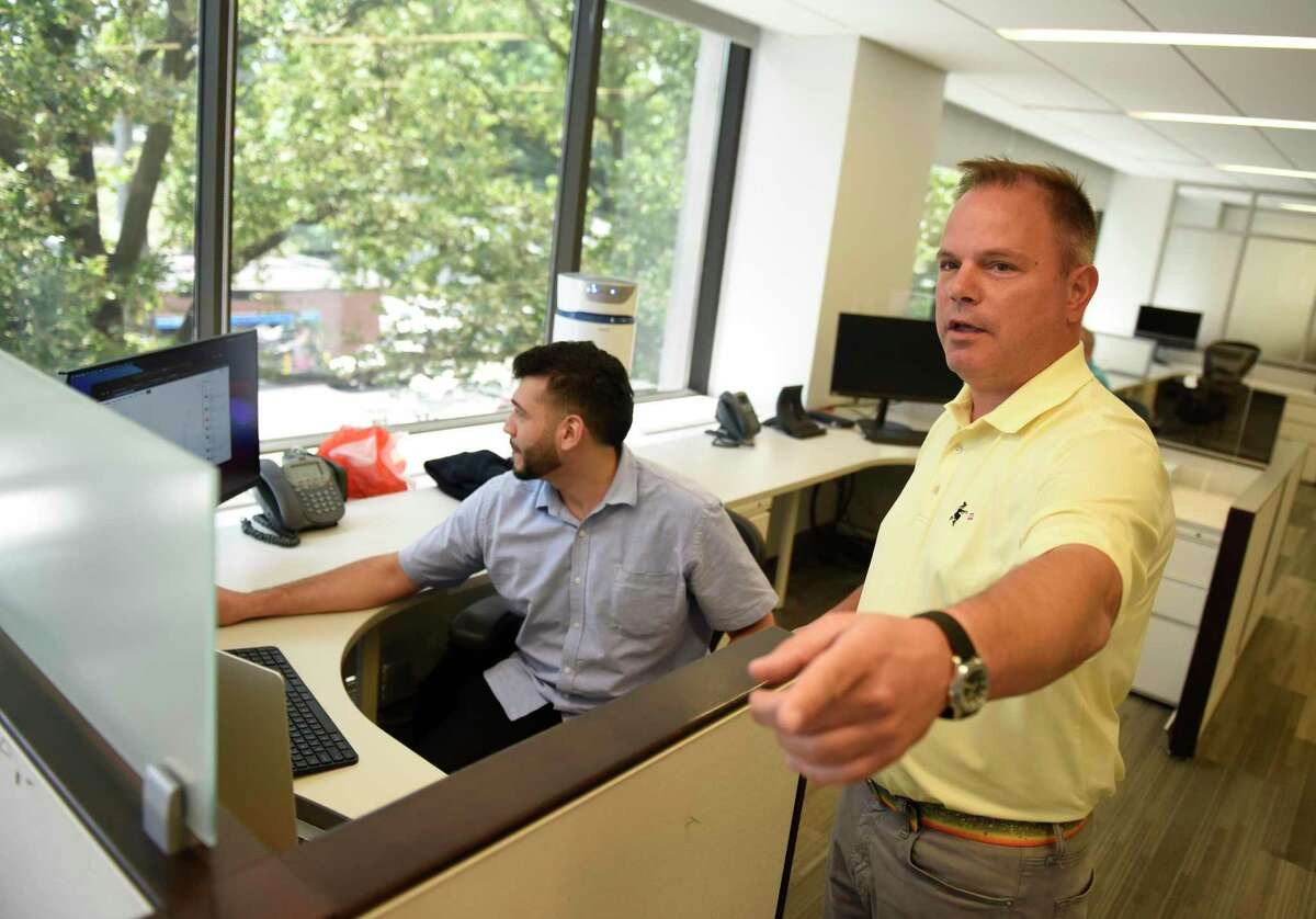 """Symbridge CEO Michael McGuire, right, works with his colleagues at the Symbridge headquarters in Greenwich, Conn. Wednesday, July 14, 2021. Symbridge promotes a new model for a digital exchange that allows investors to buy and sell cybercurrencies as well as other digital """"tokens"""" that assign value to tangible items."""