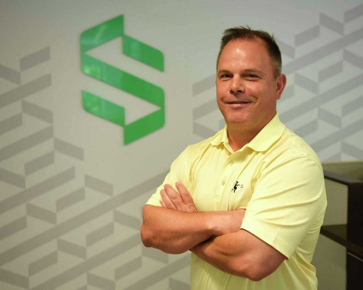 """Symbridge CEO Michael McGuire poses at the Symbridge headquarters in Greenwich, Conn. Wednesday, July 14, 2021. Symbridge promotes a new model for a digital exchange that allows investors to buy and sell cybercurrencies as well as other digital """"tokens"""" that assign value to tangible items."""