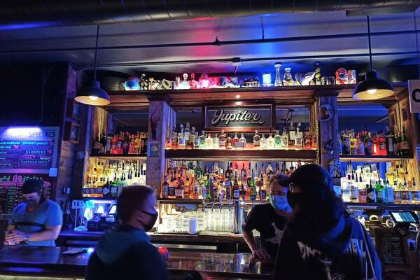 Masked patrons and bartenders interact at Jupiter Bar in Seattle.