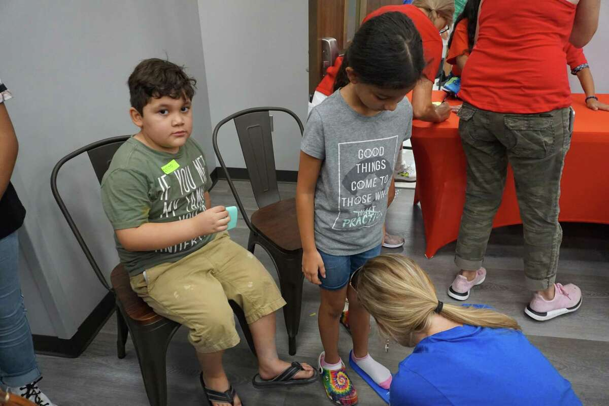 Liam Marines waits as his sister Hailyee Morales is fitted for shoes at Common Threads in Richmond during the Hope on the Brazos event on Friday, July 30.
