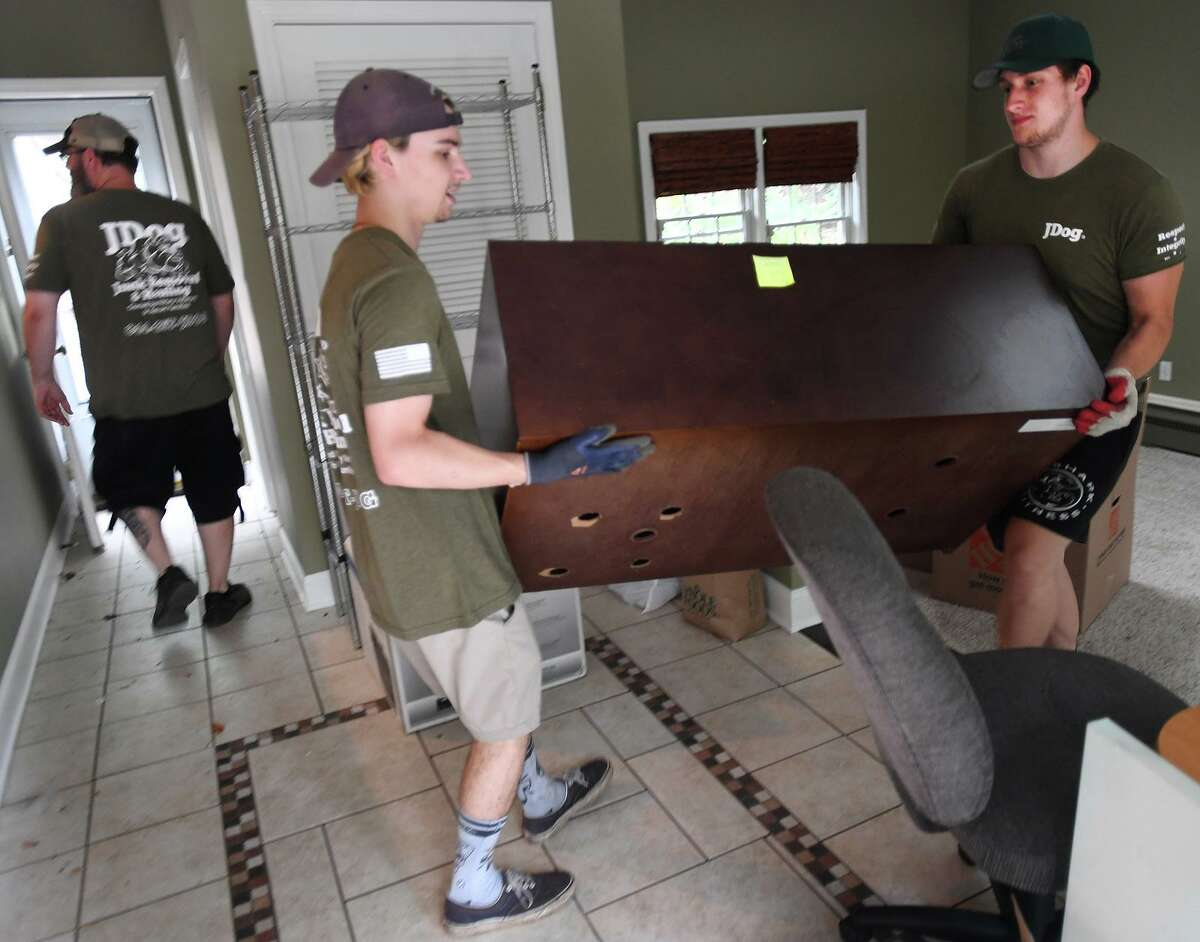 From left; JDog crew members Brian Sargent, James Carcano, and Jack Price clear out a home in preparation for sale in Milford, Conn. on Thursday, July 29, 2021.