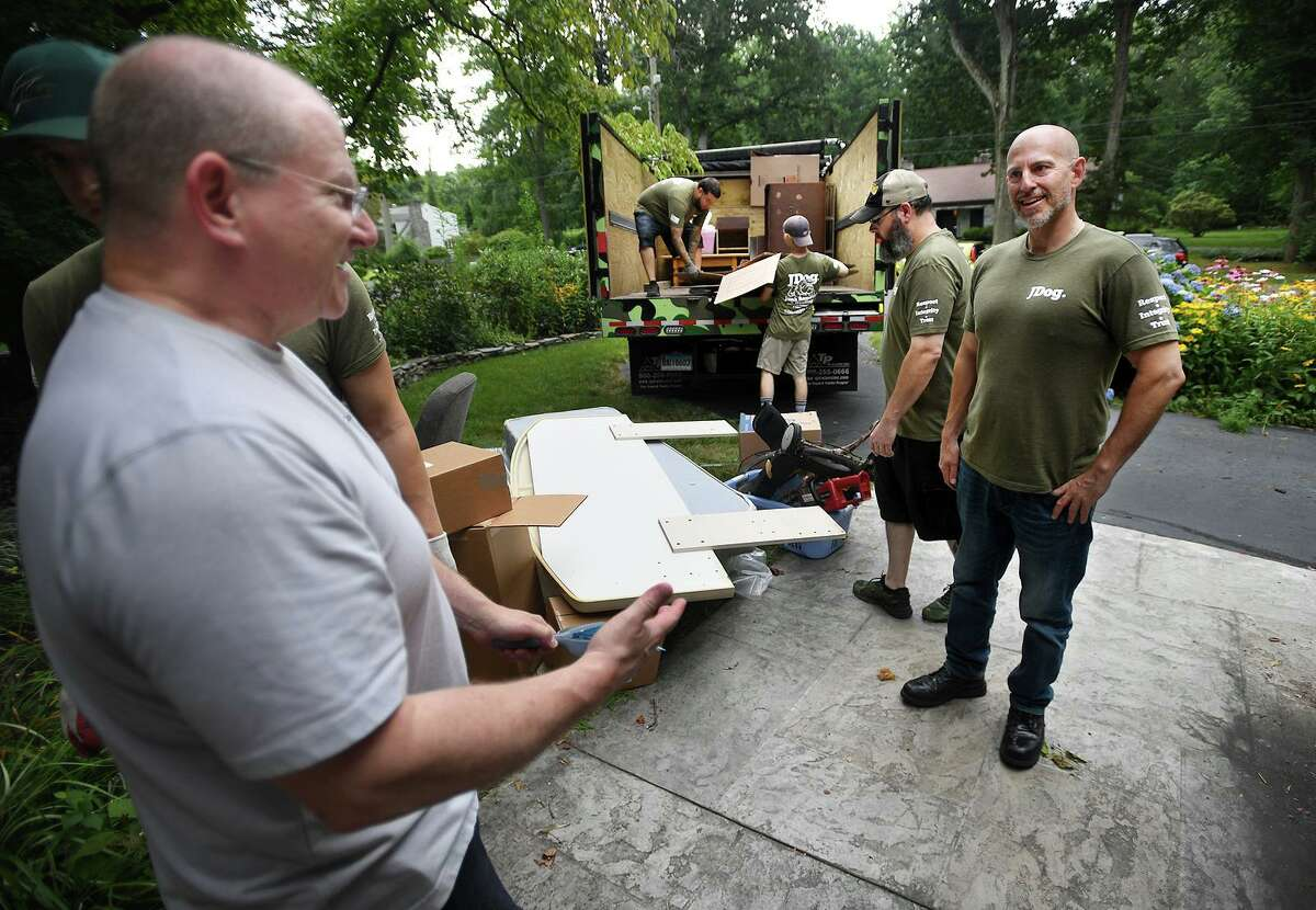 JDog owner Sean-Michael Green, right, chats with client William Murray as his crew of military vets clears out Murray's home in preparation for sale in Milford, Conn. on Thursday, July 29, 2021.