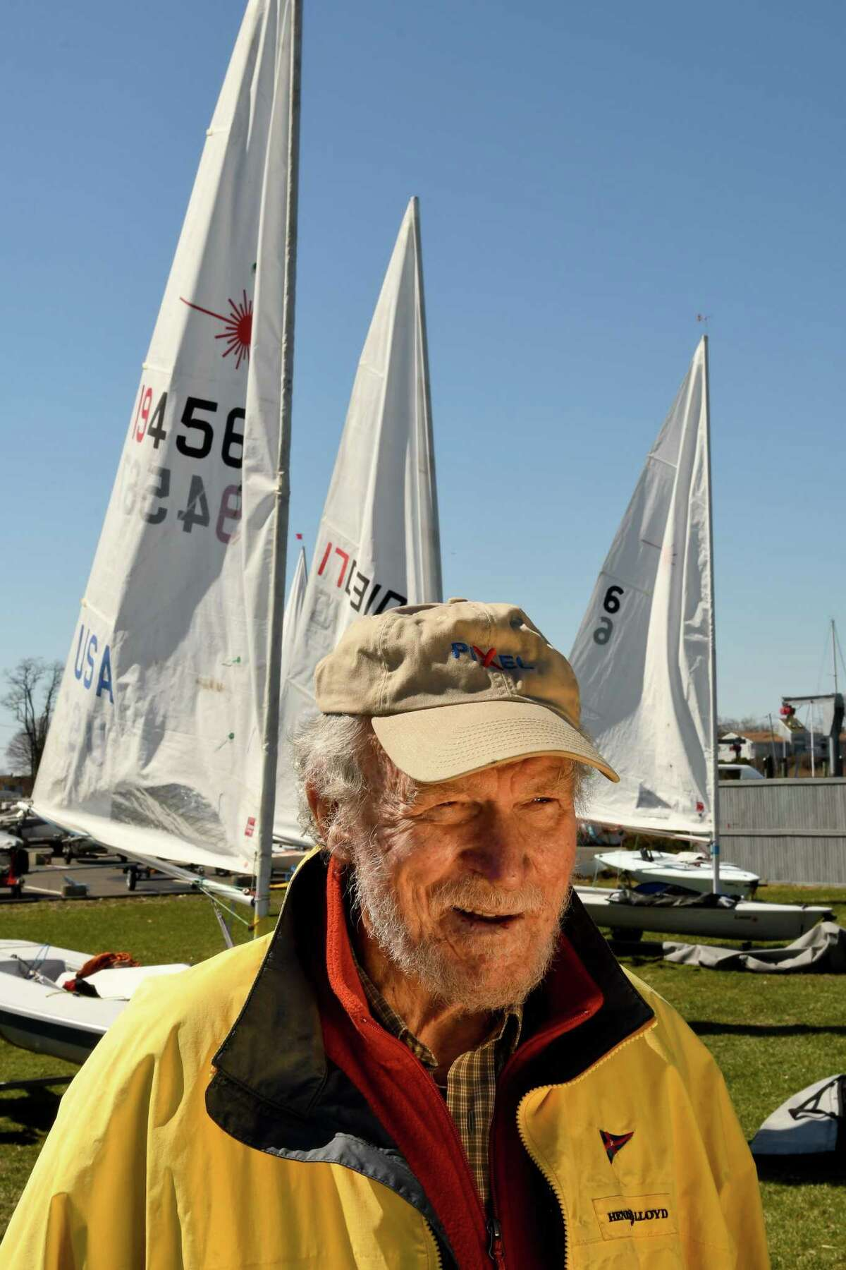 Bruce Kirby in April 2017 in Westport, Conn., alongside a small flotilla of Laser sailboats of his design.