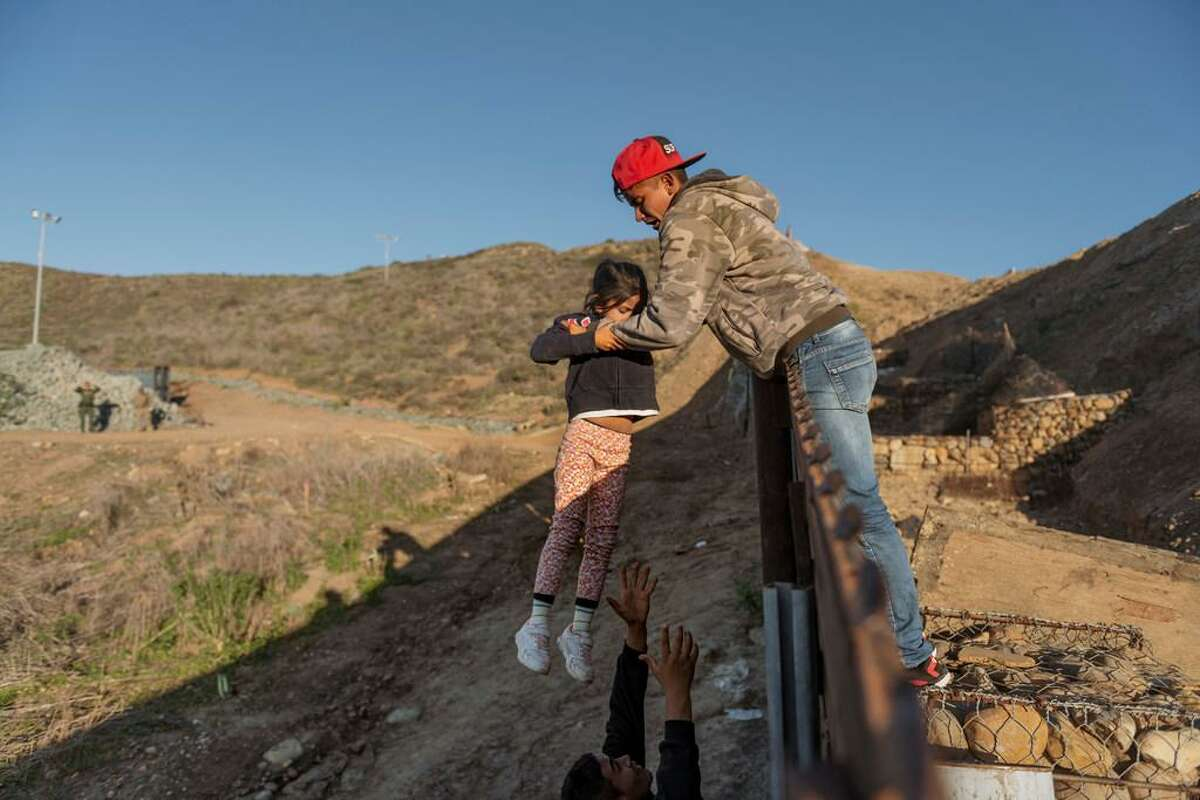 A migrant from Honduras passes a child to her father after he jumped the border fence from Tijuana to get into the U.S.