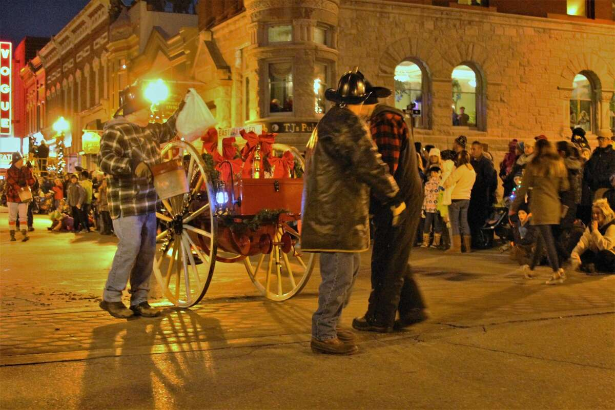 Eastlake firefighters pull an over 100-year-old piece of firefighting equipment through downtown Manistee at a past Victorian Sleighbell Parade. The cart will be transferred from storage at a marina building back to the department.