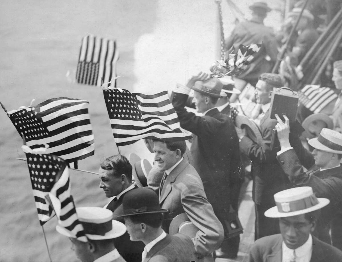 American athletes wave flags and take photographs as they set sail for the 1920 Olympics in Antwerp, Belgium.