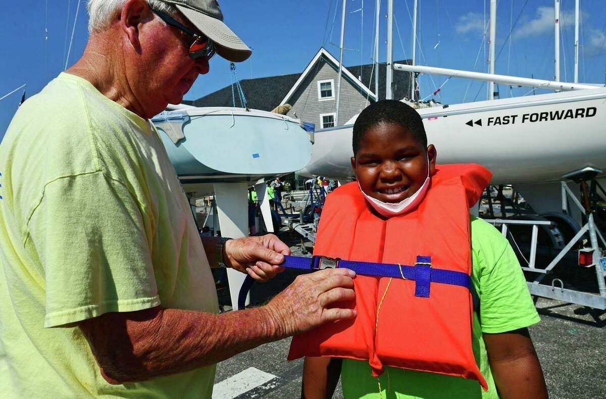 Wes Oliver helps Campers from ROSCCO (Rogers School Community Center Organization) summer vacation program including Nojah Dior Dixon, 9, get ready for a day on the water during the Noroton Yacht Club's 25th annual Boat/Camp Friday July 30, 2021, at the Yacht Club in Darien, Conn. Person-to-Person, Darien Boat Club, Darien Police Marine Unit, Noroton Fire Department, Norwalk Seaport Association, United States Coast Guard Auxiliary--Norwalk Flotilla 72 and Darien Sail and Power Squadron partner to provide a safe on-the-water experience for underserved children.