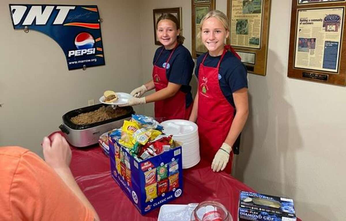 Lily Freer, right, and a friend help serve sloppy Joes Thursday at Christmas in July, sponsored by Freer and her sister, Taylor, at Freer Auto Body in Godfrey. Now in its 13th year the event raised $49,612 for Community Christmas sponsored by The Telegraph and the United Way.