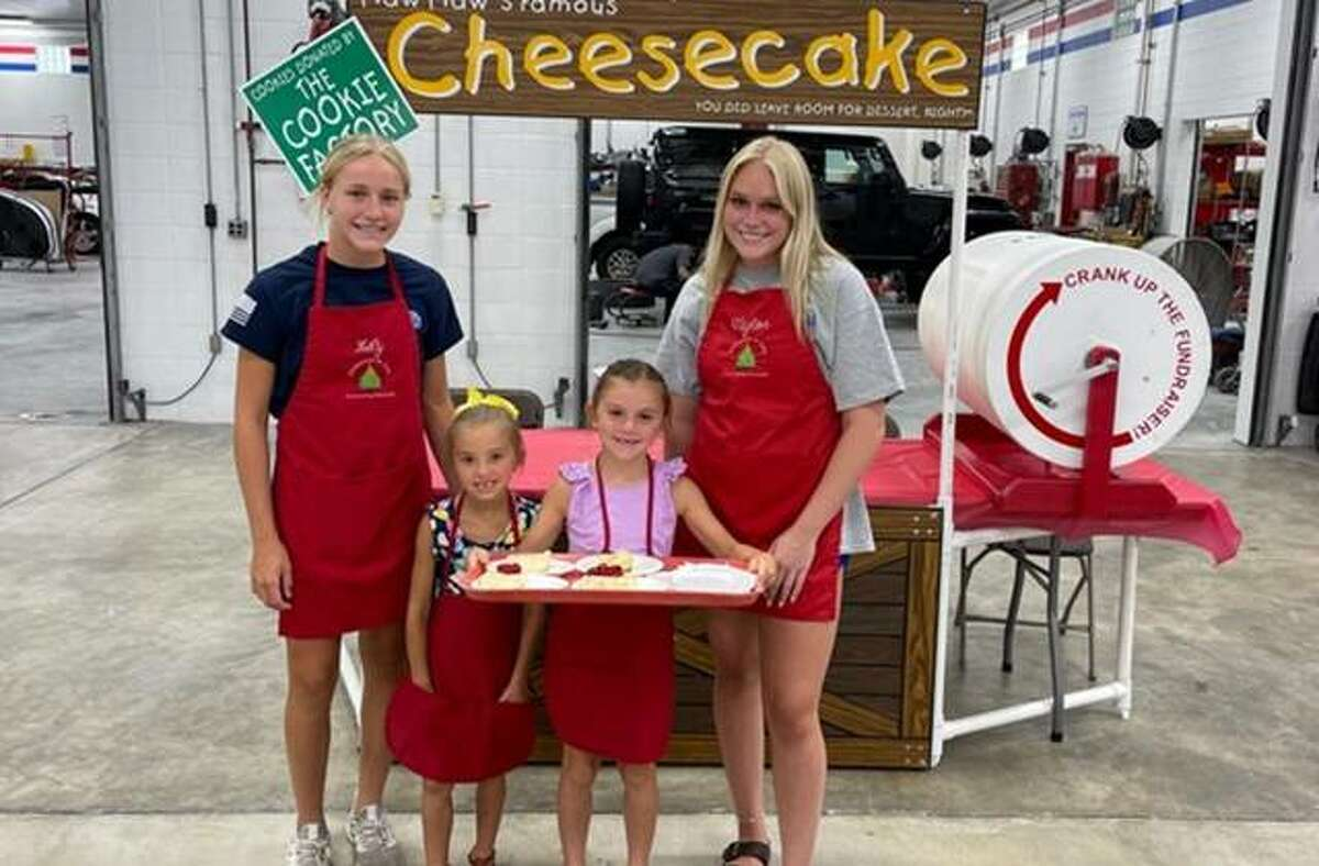 Lily Freer, left, and Taylor Freer, right, with little helpers Thursday at the annual Christmas in July event, which kickstarts annual fundraising for Community Christmas, sponsored by The Telegraph and the United Way.