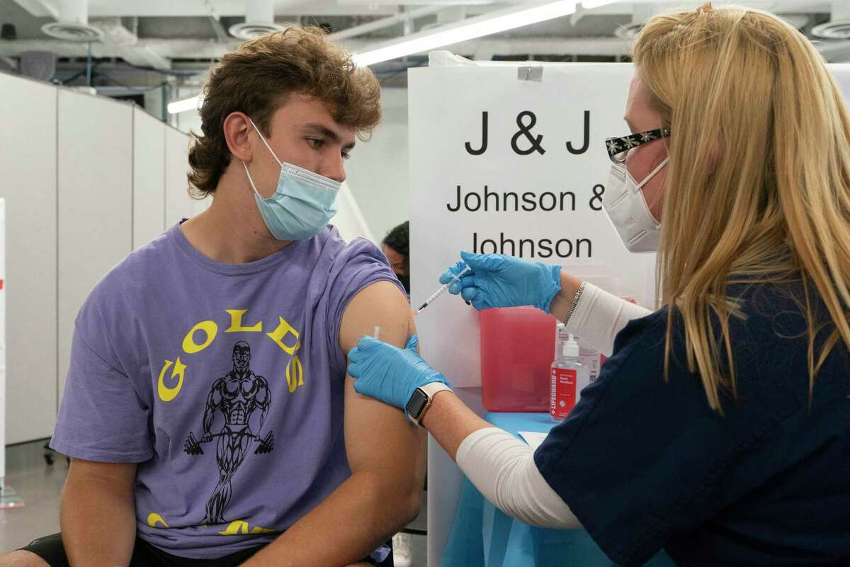 FILE-Bradley Sharp, of Saratoga, N.Y., gets the Johnson & Johnson vaccine from registered nurse Stephanie Wagner, Friday, July 30, 2021 in New York. Sharp needs the vaccination because it is required by his college.
