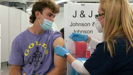 Bradley Sharp, of Saratoga, N.Y., gets the Johnson & Johnson vaccine from registered nurse Stephanie Wagner, Friday, July 30, 2021 in New York. Sharp needs the vaccination because it is required by his college. Amid increasing concern over the spread of the Delta variant, New York City announced on Wednesday that anyone can receive $100 if they get the first dose of the COVID-19 vaccine at any city-run vaccination clinic.
