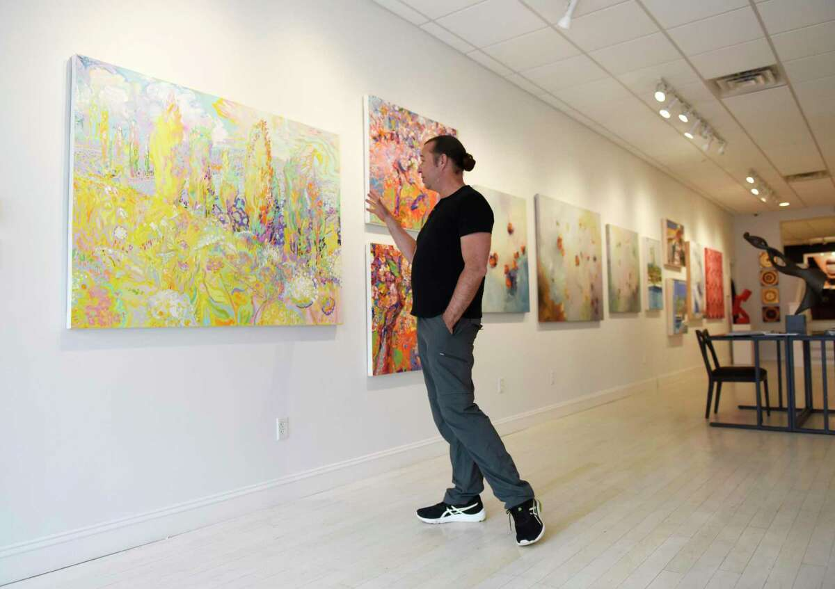 Managing Director and Co-Owner Alex Trimper shows an impressionist painting by Dmitri Wright at Isabella Garrucho Fine Art in Greenwich, Conn. Thursday, July 29, 2021.