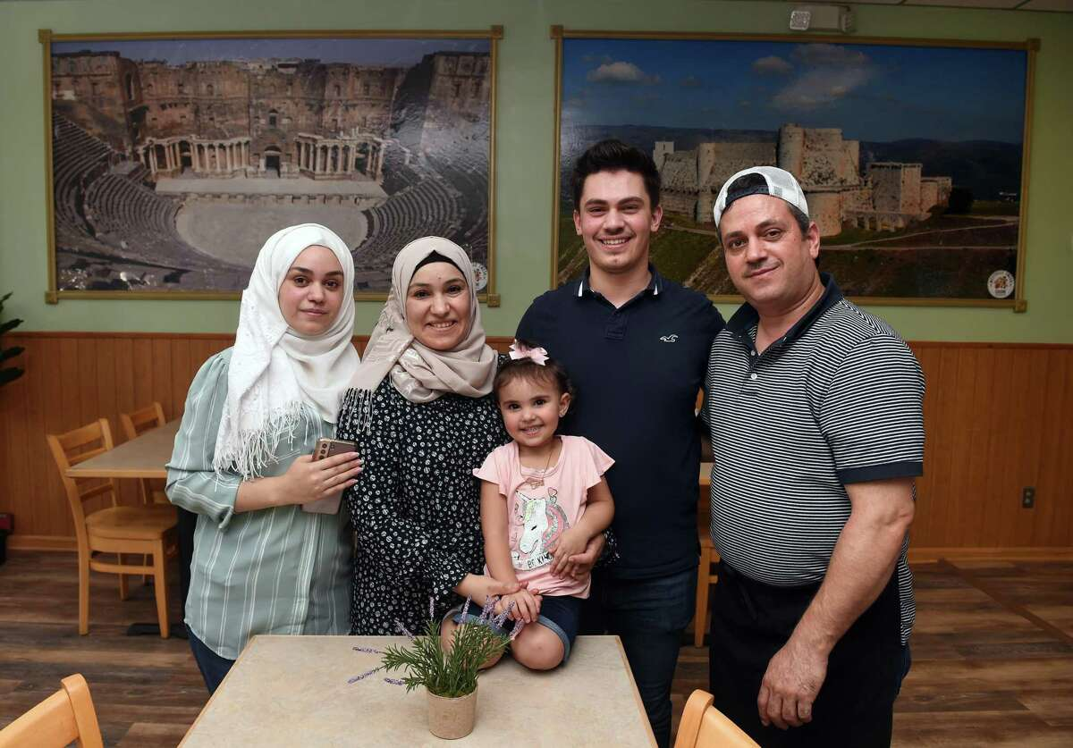 From left, Ghena Alsaloumi, with her mother, Rawan Oudeh, sister, Eleen Alsaloumi, brother, Ayman Alsaloumi, and father, Mazen Alsaloumi, at Westville Emesa on Whalley Avenue in New Haven. In the background are photographs of a Roman theater (left) in Daraa, Syria and a castle in Homs, Syria, Qala'at al-Hosn.