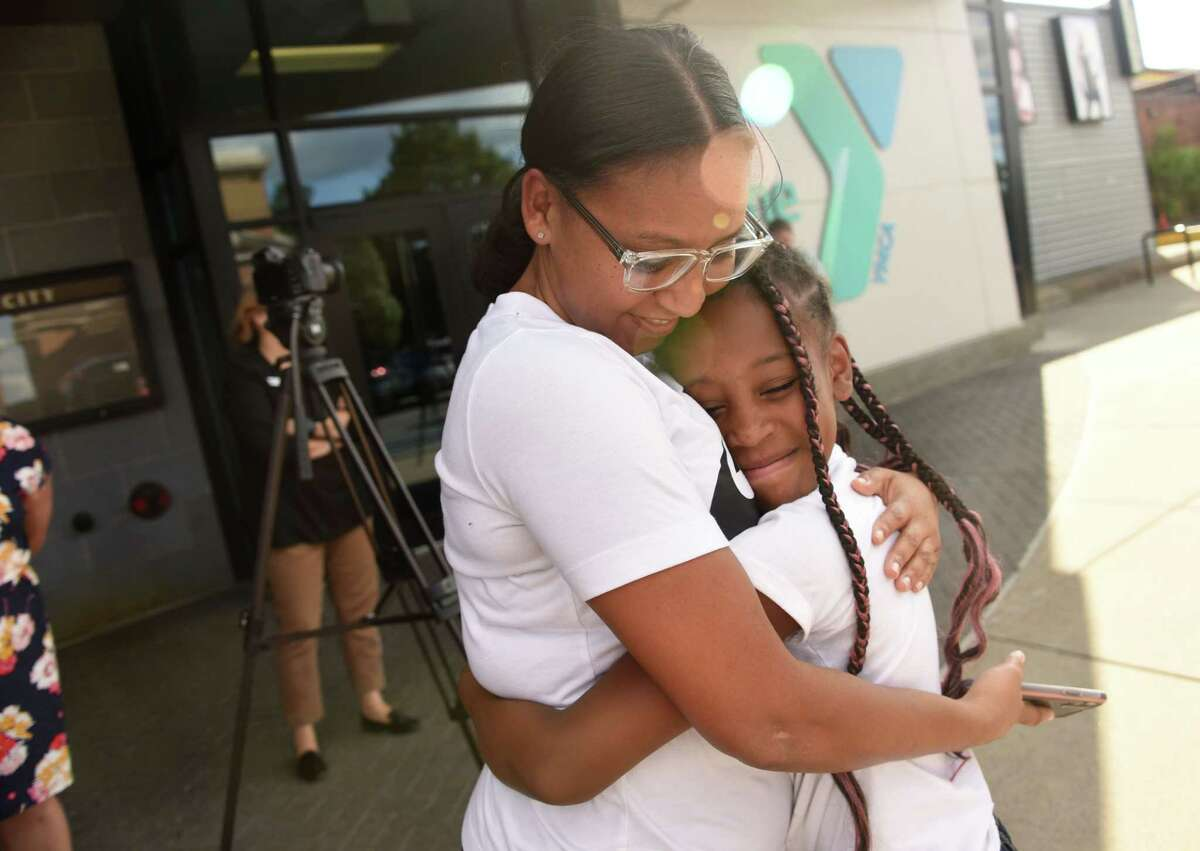 Jani Mixon, 10, of Brooklyn hugs her mother Nikki Farley after departing the bus from YMCA's Camp Chingachgook in Lake George on Friday, July 30, 2021 in Schenectady, N.Y. The parents waited for the bus behind the YMCA. (Lori Van Buren/Times Union)
