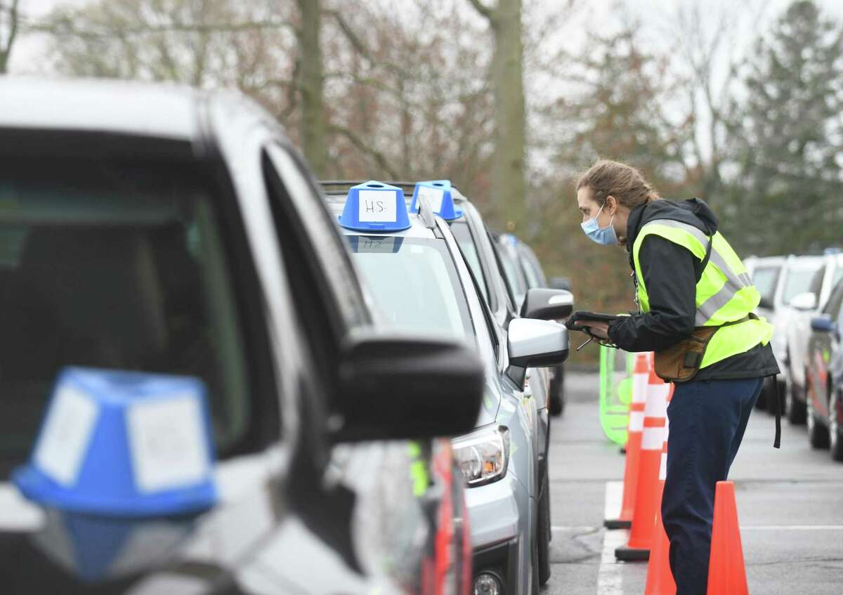Clinical vaccinator Kyra Ischer checks in patients waiting to be vaccinated at the Community Health Center Drive-Thru Vaccination Clinic in Stamford on April 11, 2021. CHC has since shuttered the drive-through clinic.