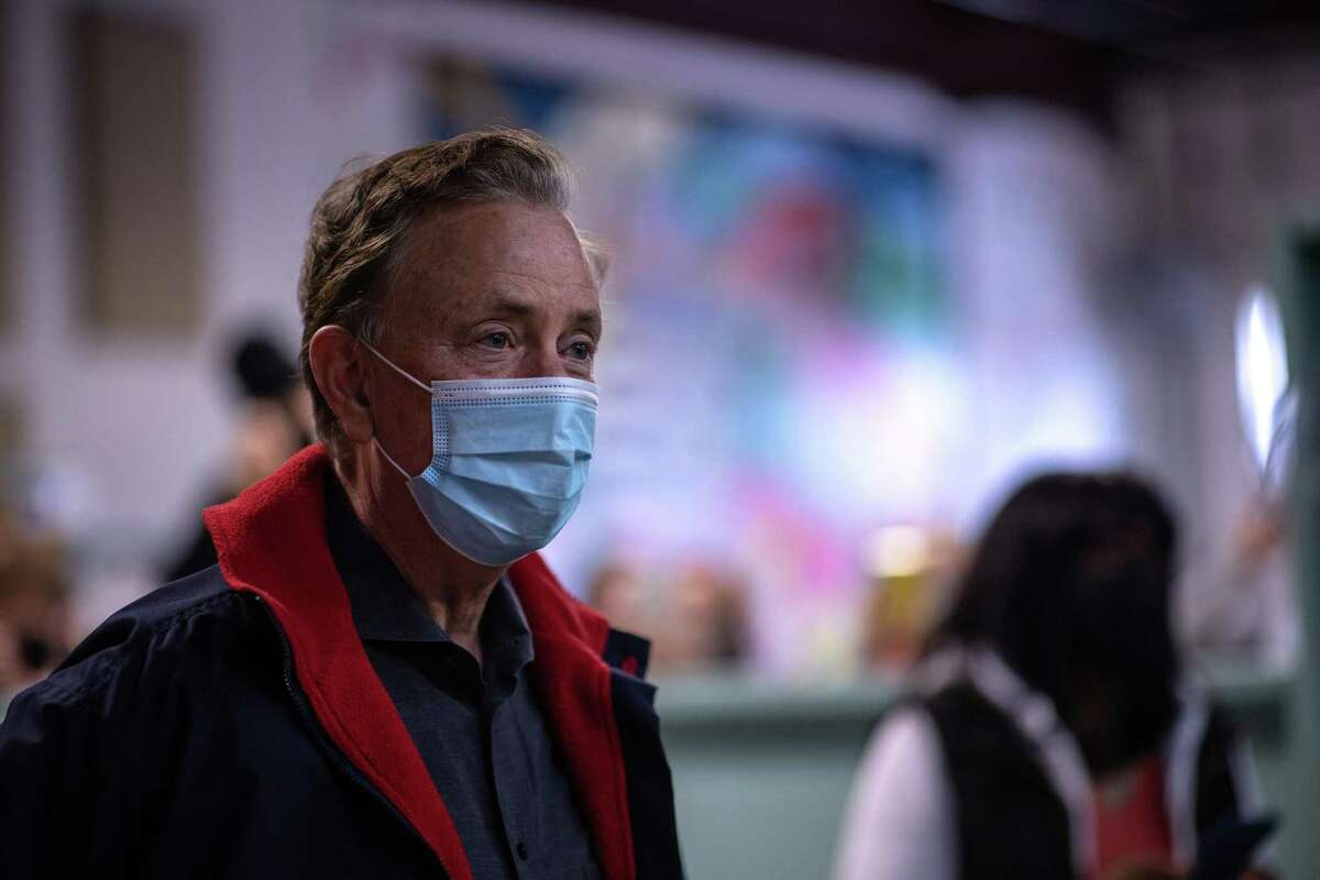 Governor Ned Lamont watches as immigrants are vaccinated at a COVID-19 community vaccination clinic on March 14, 2021 in Stamford.