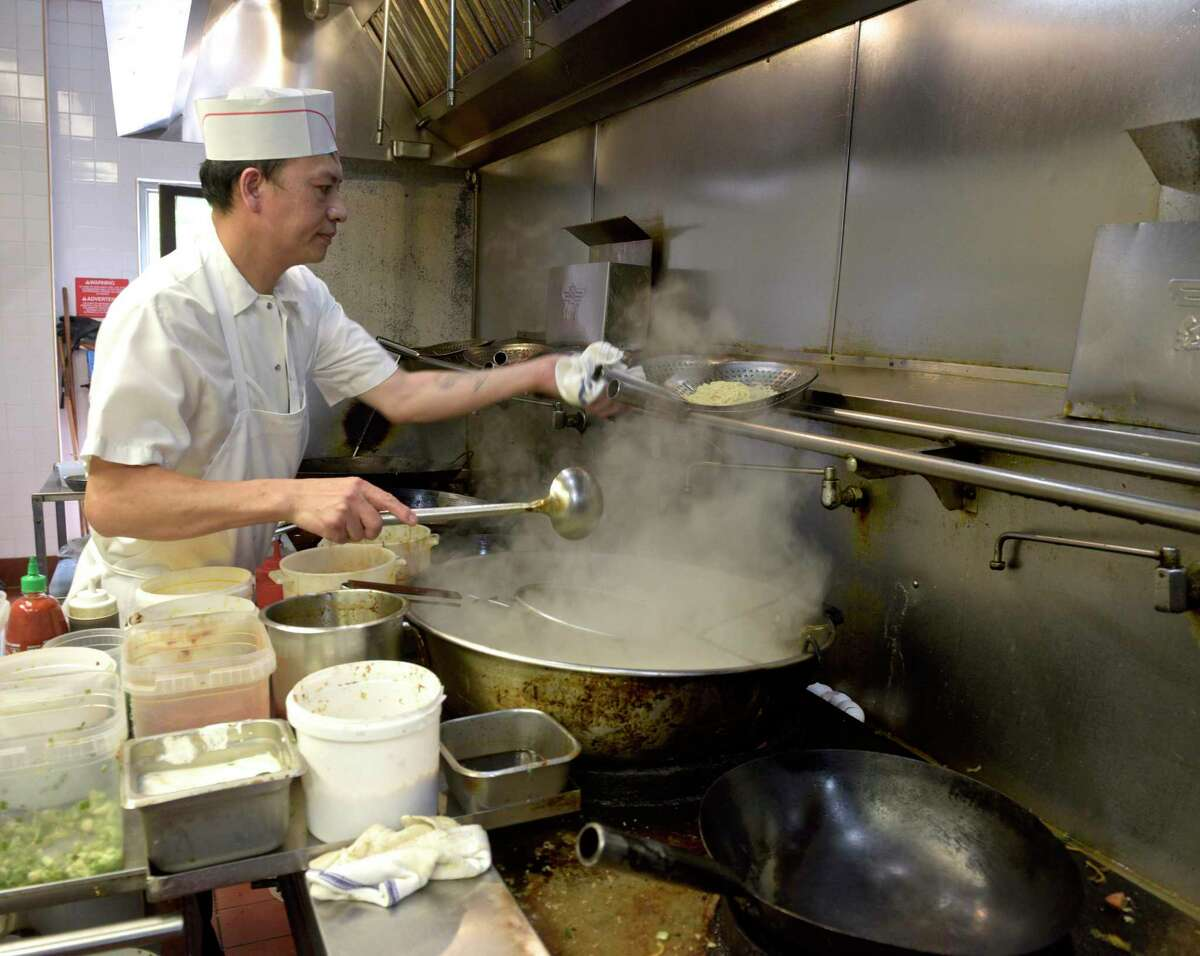 Chef Jimmy Wang prepares a lunch order on Thursday at Hunan Noodle Bar. Owner Jason Januar would like to open a third restaurant but faces staffing issues. July 29, 2021, in Ridgefield, Conn.