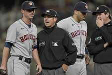 Houston Astros relief pitcher Brooks Raley, left, talks with umpire Tripp Gibson, second from left, after Raley was ejected from a baseball game against the Seattle Mariners after he hit Seattle Mariners' J.P. Crawford with a pitch during the eighth inning, Monday, July 26, 2021, in Seattle. The Mariners won 11-8. (AP Photo/Ted S. Warren)