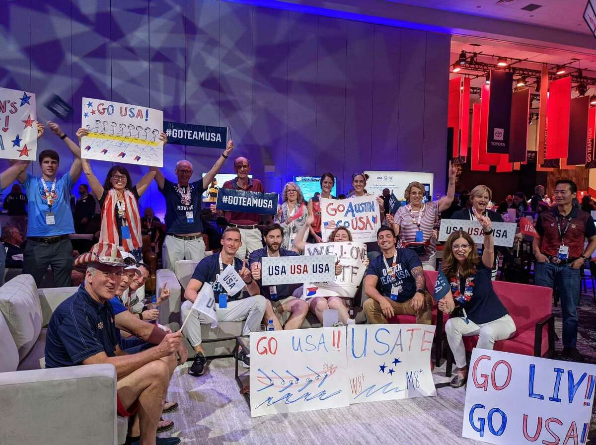 Greg Hack, left in cowboy hat, Joan Corrigan, behind Hack in red and white scarf, and Brian Corrigan, right of Joan, cheer on Team USA with families of other Olympic rowers at a watch party in Orlando, Fla. The watch party was organized by the U.S. Olympic Committee and NBC to provide families of athletes a private experience to watch the 2020 Tokyo Games.