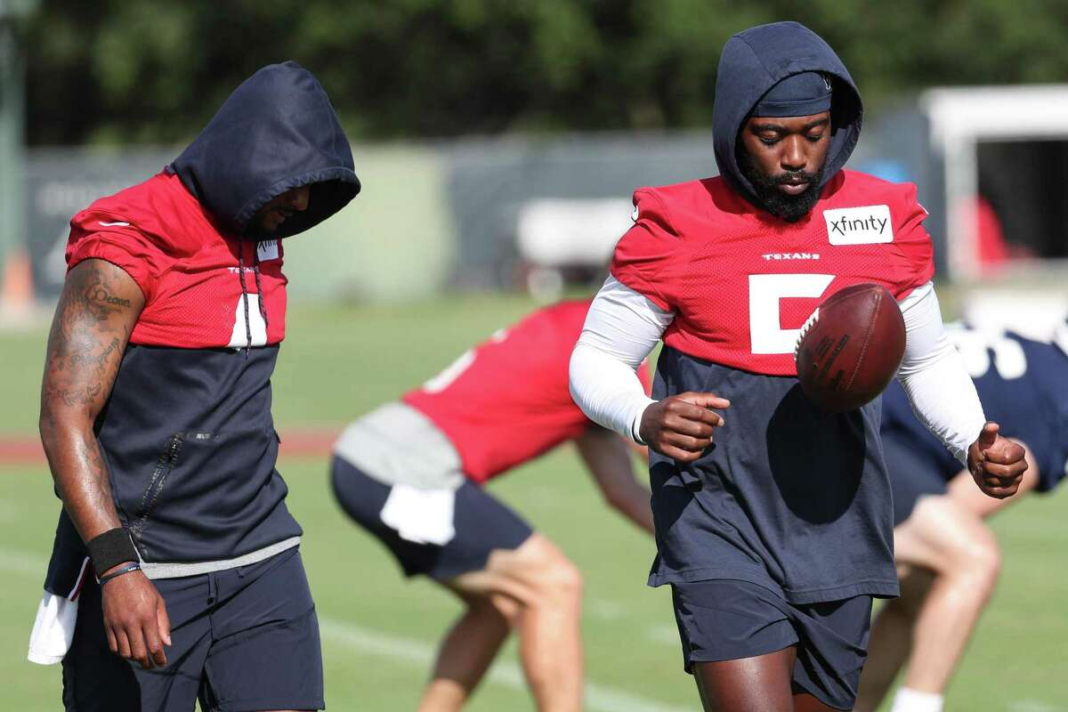 Houston Texans quarterbacks Deshaun Watson (4) and Tyrod Taylor (5) walk to the next drill together during an NFL training camp football practice on Friday. Taylor was absent Saturday.