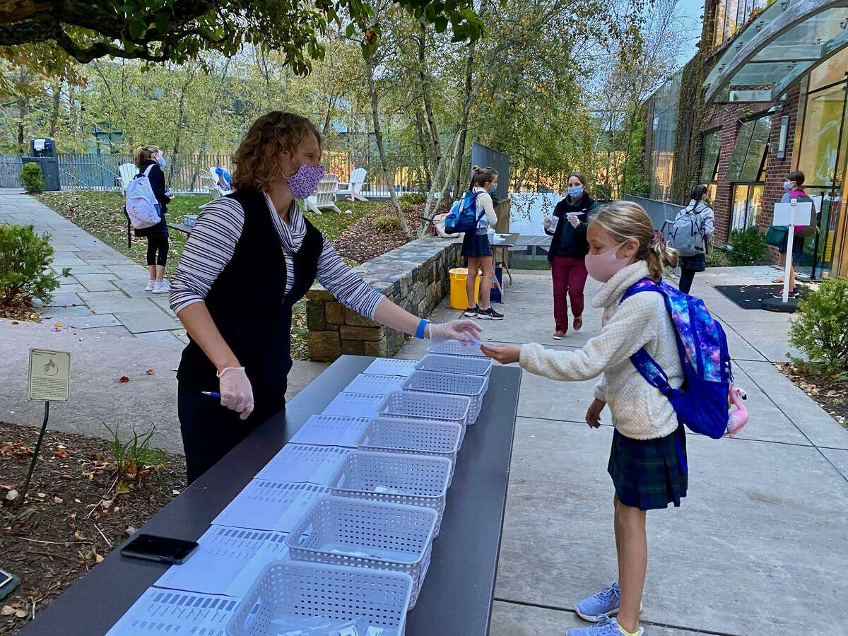 Michelle Summers, Greenwich Academy's director of finance and operations and Covid coordinator, collects a saliva sample to be tested for Covid at the school in Greenwich, Conn.