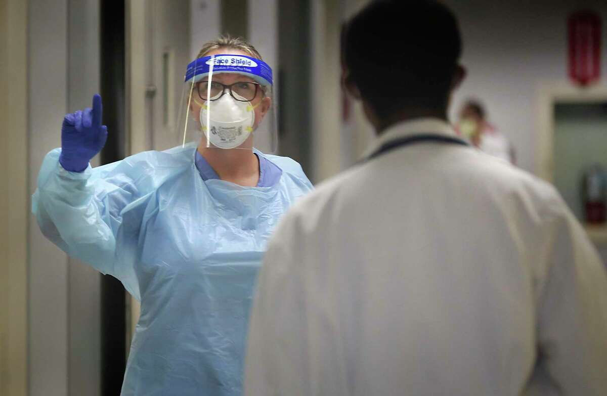 Shiela Sandoval, left, a nurse in one of the four covid units at Methodist Hospital, talks with Dr. Timothy Osonma about a patient. San Antonio has had a massive influx of coronavirus patients into its hospitals, on Thursday, June, 25, 2020.