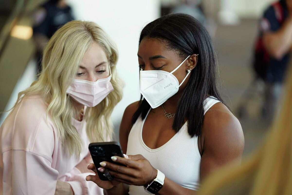 Simone Biles looks at her phone with teammate Mykayla Skinner, left, during a United Airlines send-off event for the U.S. Women's Gymnastics team at the San Francisco International Airport on Wednesday, July 14, 2021.