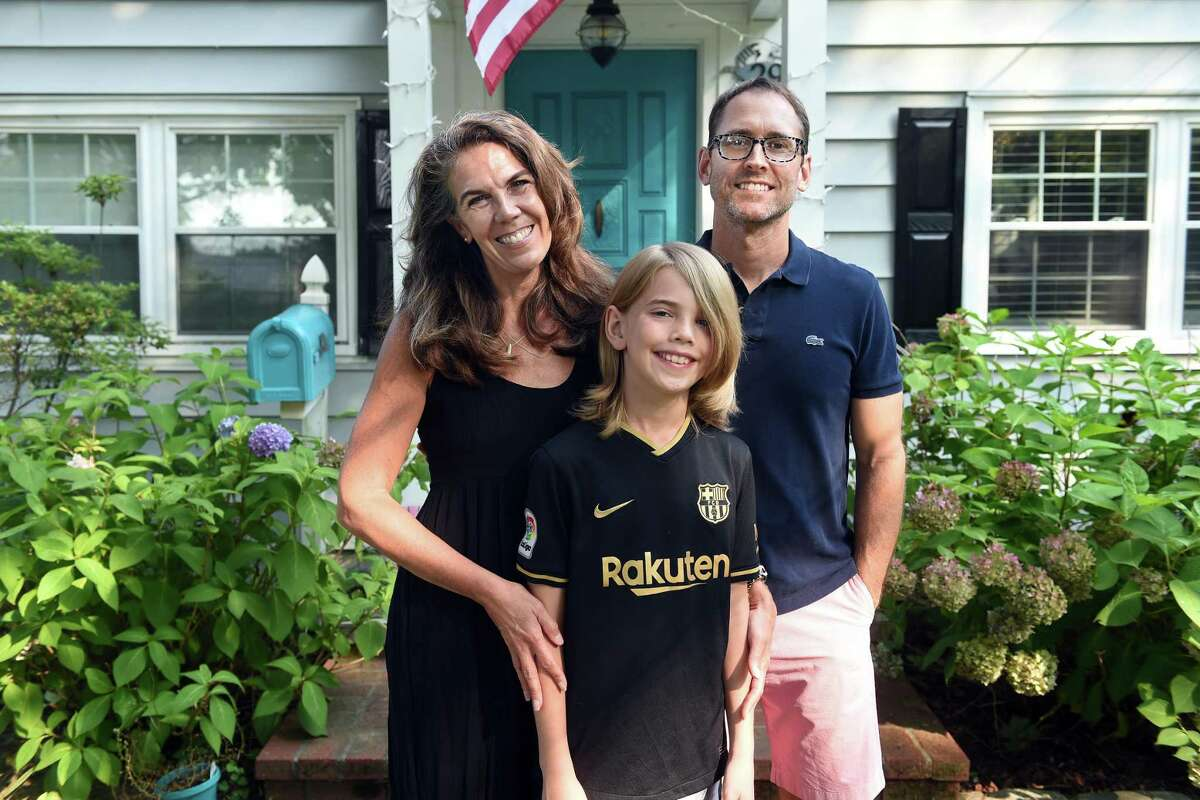 From left, Marney White, her son, Lane Mayville, and husband, Erik Mayville, photographed in front of their home in Fairfield on Tuesday.