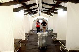 Staff look inside the mobile medical unit at Baptist Hospital, which was installed as COVID-19 cases rapidly increase, taxing emergency rooms and hospitals. The outdoor tent will be used to treat and release non-COVID patients with minor emergencies. Photo made Friday, July 30, 2021 Kim Brent/The Enterprise