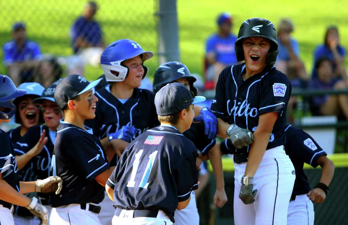Wilton's Cole Herbst, right, celebrates with teammates after hitting a home run against Waterford in the Little League state championship tournament in Stamford on Friday.